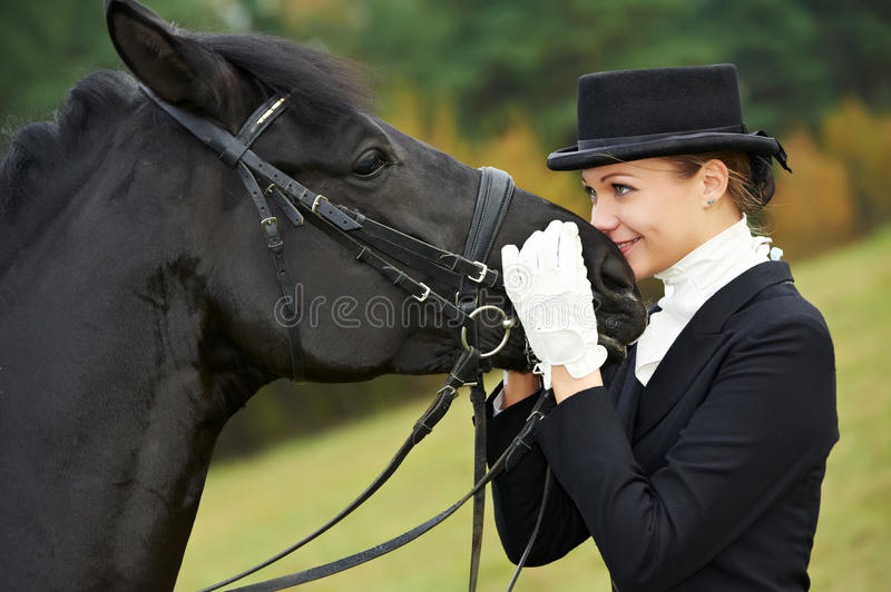 Horsewoman jockey in uniform with horse. Horsewoman jockey in uniform standing with horse outdoors stock photography