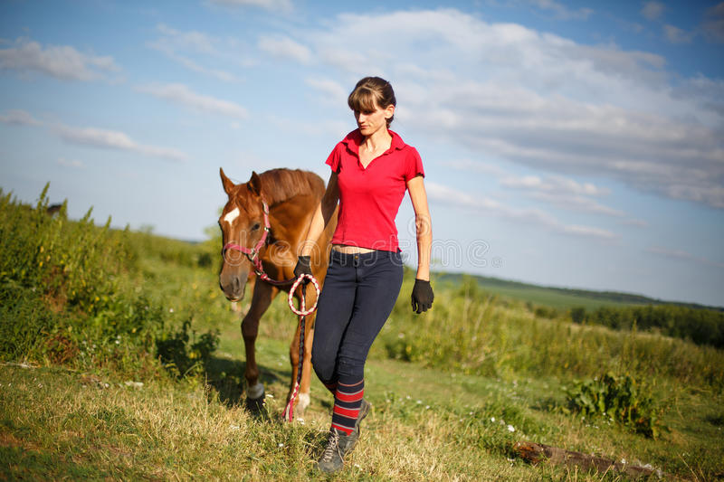 Horsewoman jockey in uniform standing with horse. Outdoors royalty free stock image