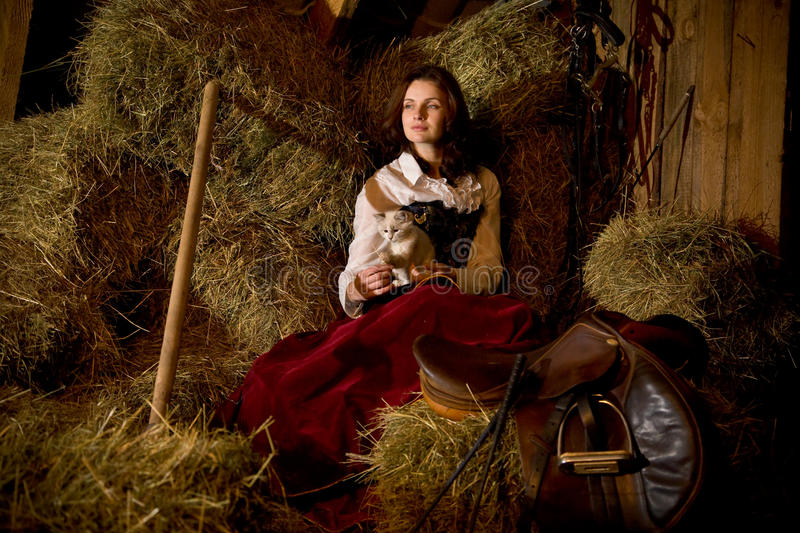 Horsewoman with a kitten. On the haystack royalty free stock photography