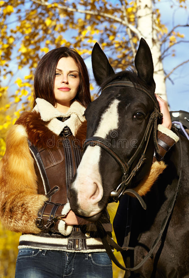 Horsewoman. Portrait of a pretty young woman with a black horse riding autumn day stock photography