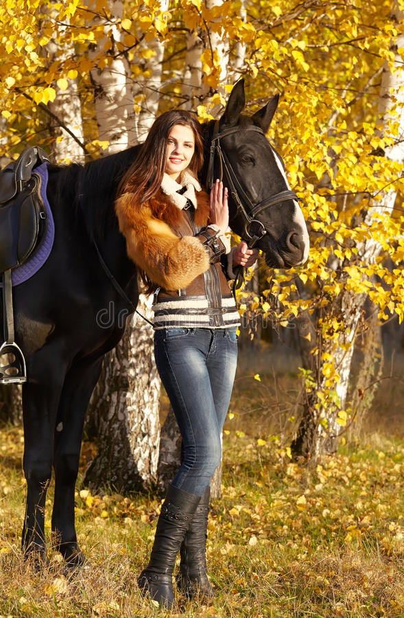 Horsewoman. Portrait of a pretty young woman with a black horse riding autumn day royalty free stock image