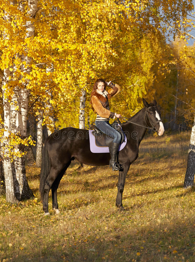 Horsewoman. Portrait of a pretty young woman with a black horse riding autumn day stock photos