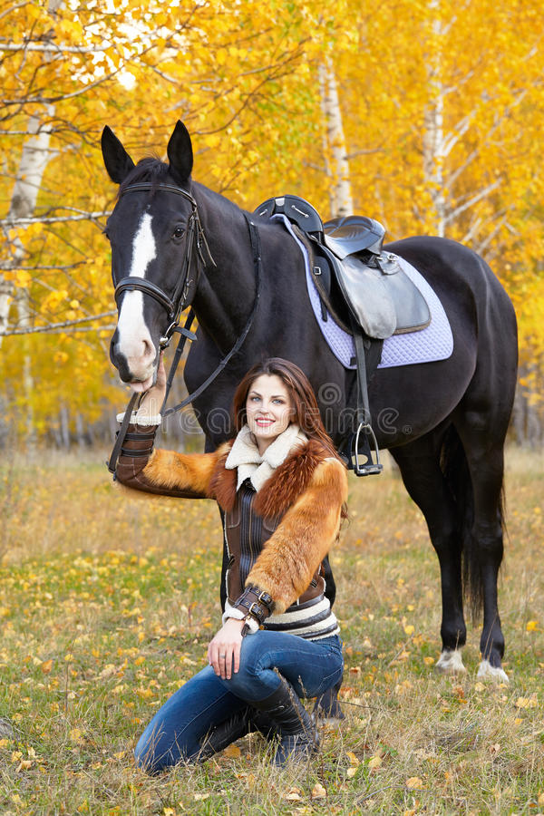 Horsewoman. Portrait of a pretty young woman with a black horse riding autumn day royalty free stock photo