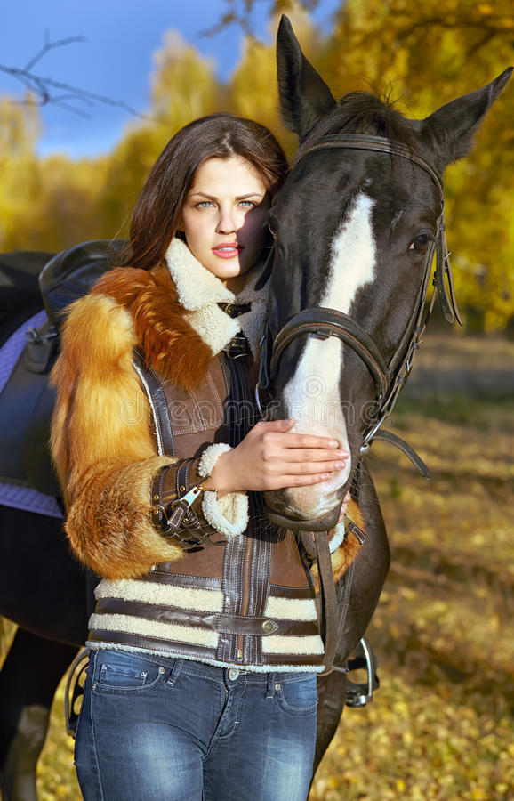 Horsewoman. Portrait of a pretty young woman with a black horse riding autumn day stock photo