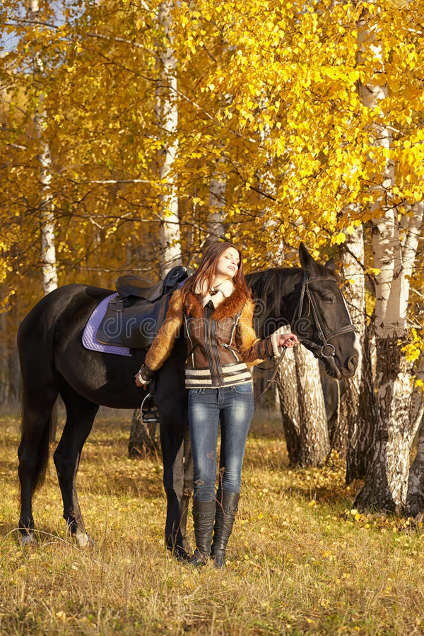 Horsewoman. Portrait of a pretty young woman with a black horse riding autumn day stock image