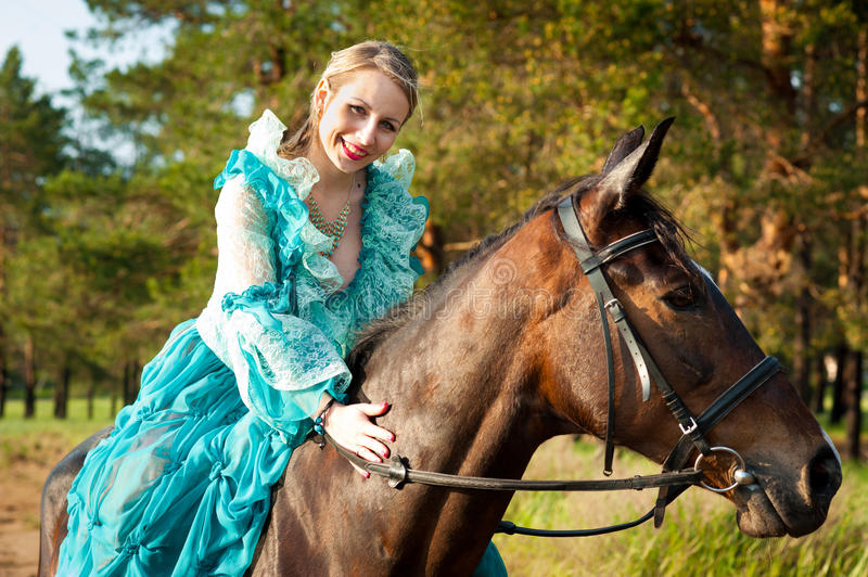Horsewoman riding. Horsewoman in blue dress riding by the dirt road royalty free stock photos