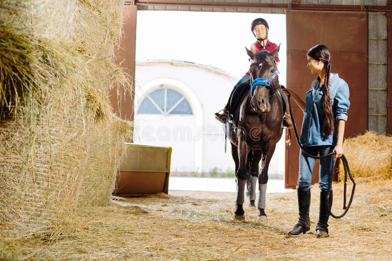 Horsewoman teaching her daughter riding racing horse. Riding lesson. Professional beautiful horsewoman teaching her cute daughter riding racing horse royalty free stock image