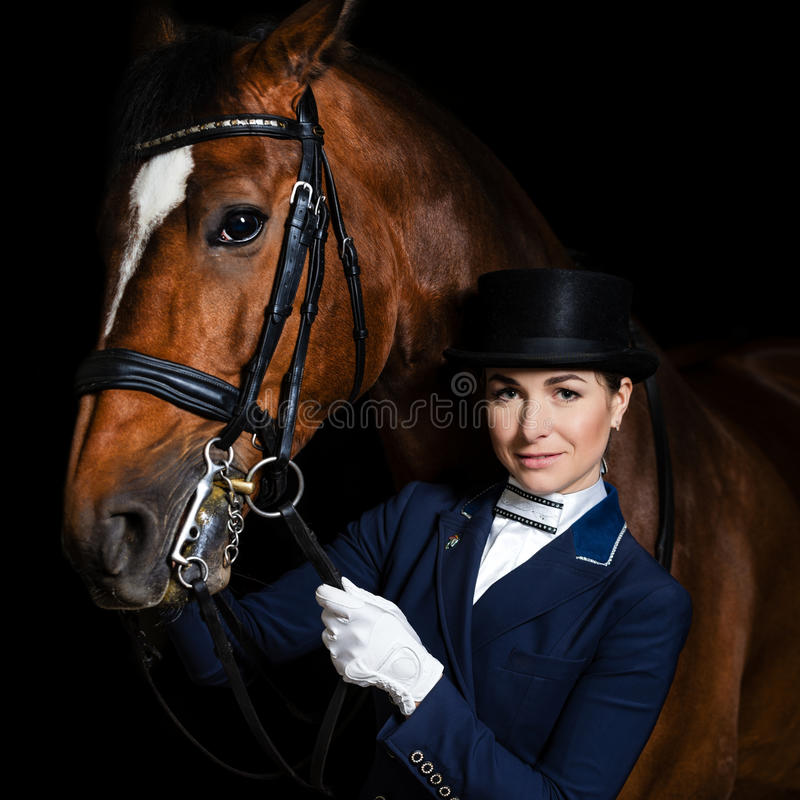 Horsewoman in uniform with a brown horse. Over dark background royalty free stock image