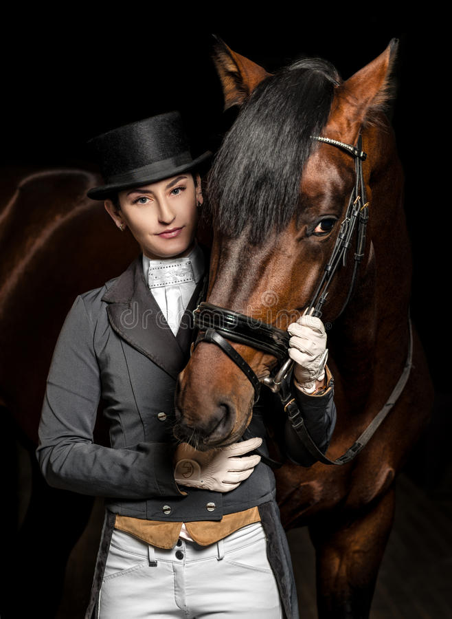 Horsewoman in uniform with a brown horse in the stable.  royalty free stock image