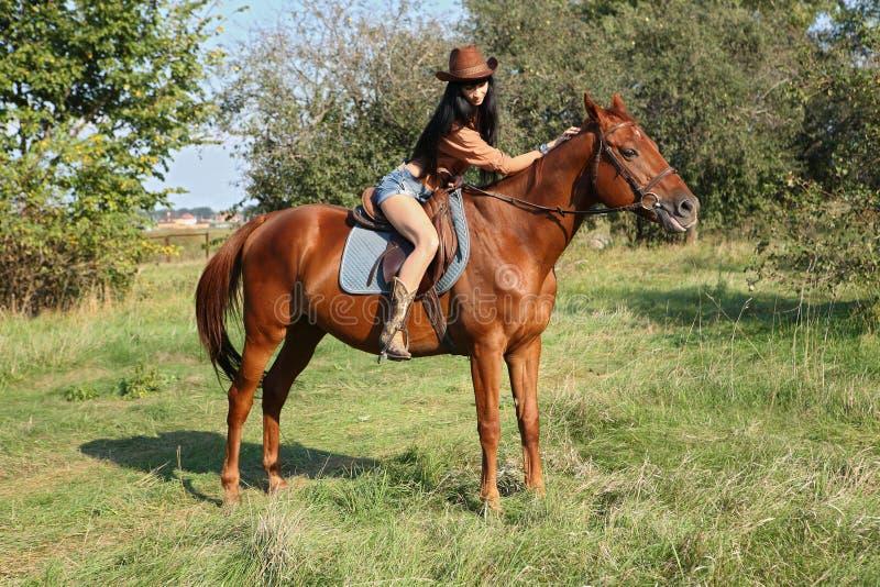 Horsewoman. Walking her horse in garden royalty free stock image