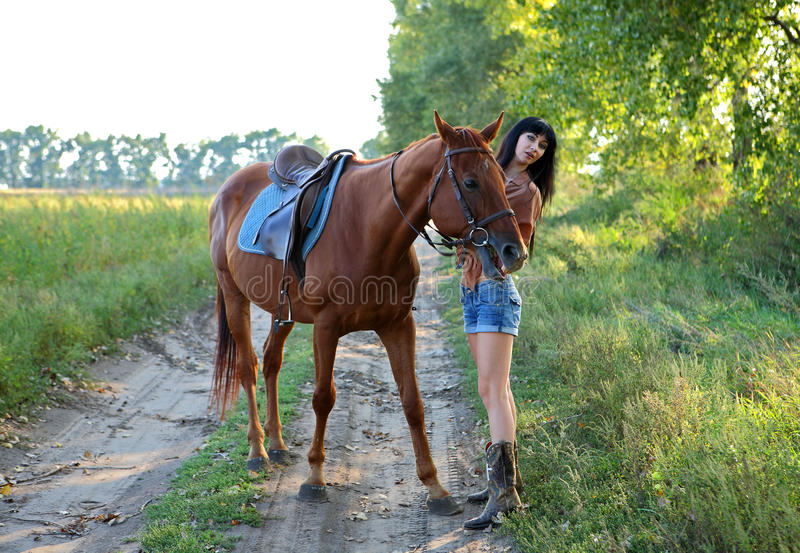 Horsewoman. Walking her horse in garden royalty free stock images