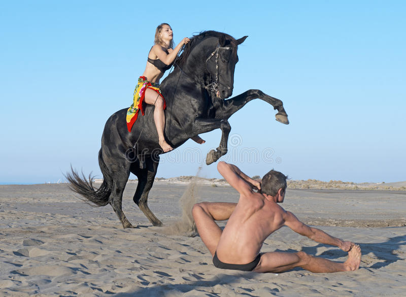 Horsewoman and yogi. Horsewoman and her horse and yogi on the beach royalty free stock photography