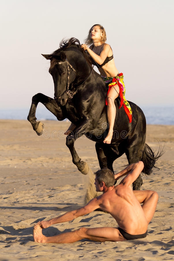 Horsewoman and yogi. Horsewoman and her horse and yogi on the beach royalty free stock image