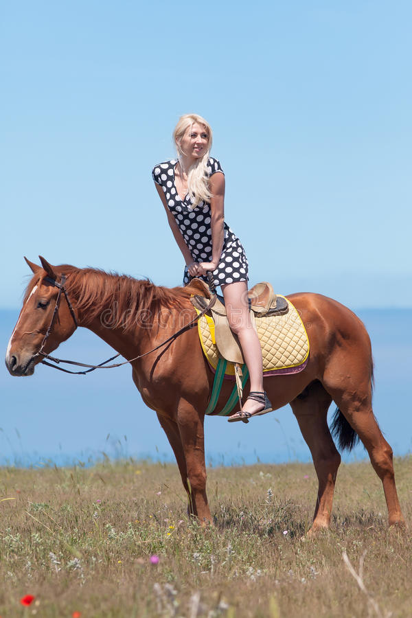 Horsewoman. Young blonde woman in polka-dot dress rides on brown gelding stock image