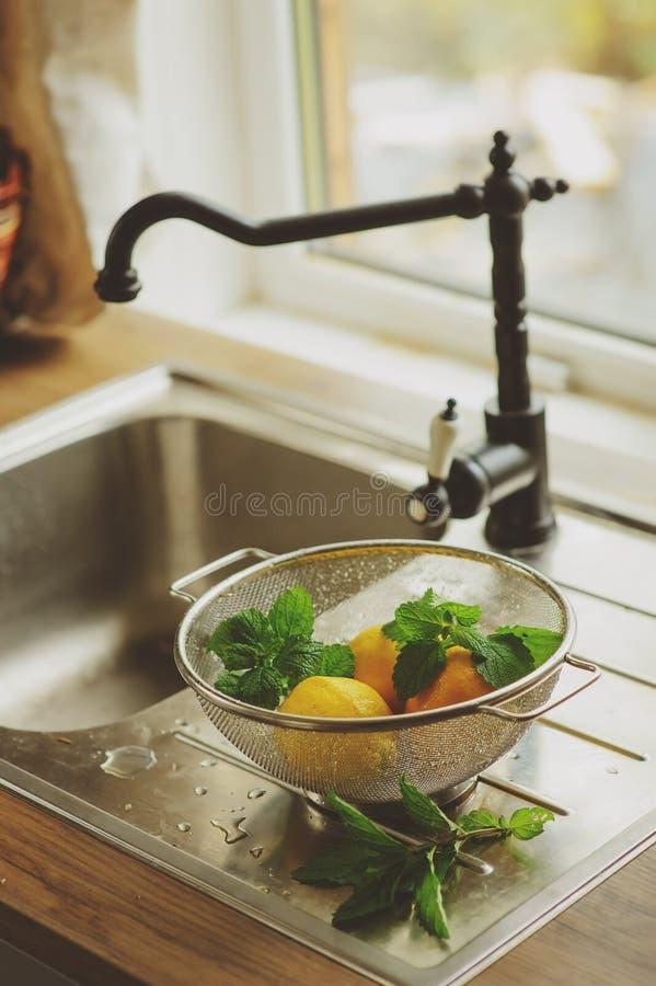 Hortelã fresca e limões na cozinha imagem de stock royalty free