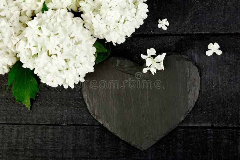 Hortensia de la flor del ramo y corazón de la pizarra en fondo de madera negro imagen de archivo