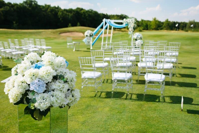 Hortensie-Blumen-Vorbereitungen für die Heirat Unscharfe Reihen von weißen Stühlen auf grünem Rasen vor einer Hochzeitszeremonie lizenzfreie stockfotos