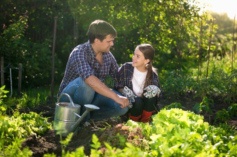Horticultura de enseñanza sonriente de la hija del padre en el jardín fotografía de archivo