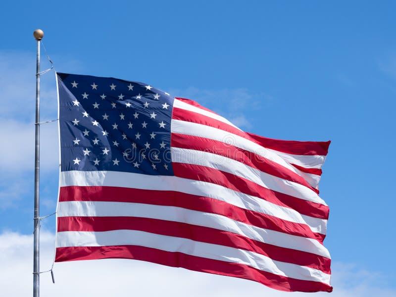 Horyzontalna Unfurled flaga ameryka?ska Przeciw niebieskiemu niebu z chmurami fotografia royalty free