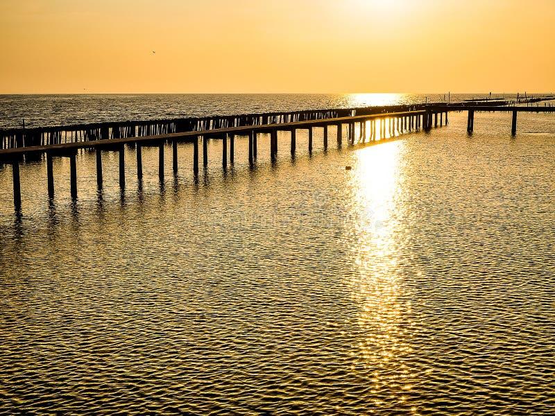 Horyzontalnego linia horyzontu Lesisty bridżowy słup w porcie między wschód słońca przeciw pomarańczowego niebo spokoju pokojowem zdjęcia royalty free
