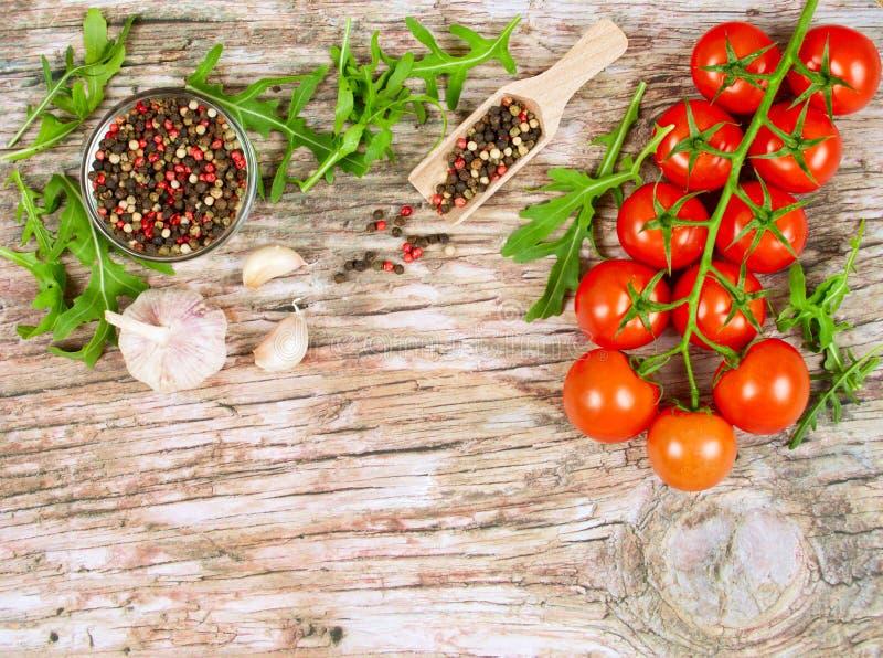 Horyzontalny karmowy sztandar z czereśniowymi pomidorami, świeżym arugula, czosnkiem i peppercorns na drewnianym tle, Opróżnia pr obraz stock