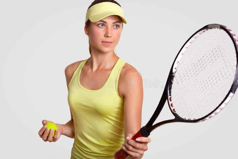 Horyzontalny portret ładny fachowy żeński gracz w tenisa trzyma racquet, chwyt piłkę, przygotowywającego robić pupila strzałowi,  zdjęcia stock