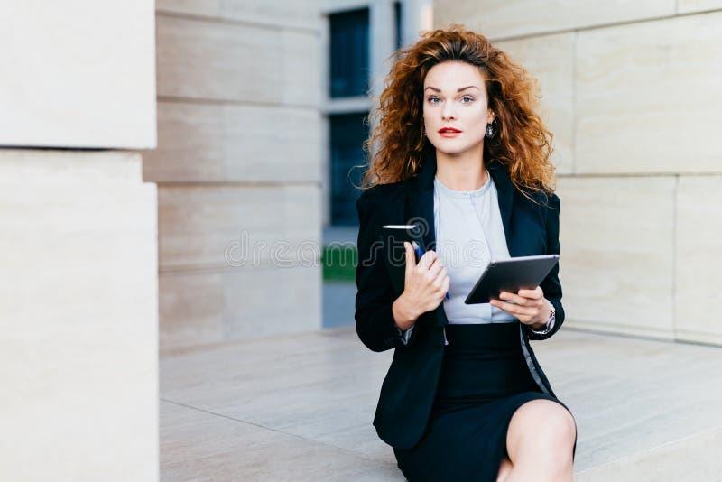 Horyzontalny portret dosyć ufny bizneswoman ubierał formalnie, trzymający jej kieszeniową książkę z pióra i pastylki komputerem,  zdjęcia stock