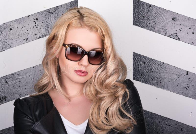 Horyzontalny portret młoda piękna kobieta w czarnych okularach przeciwsłonecznych i skórzanej kurtce fotografia royalty free