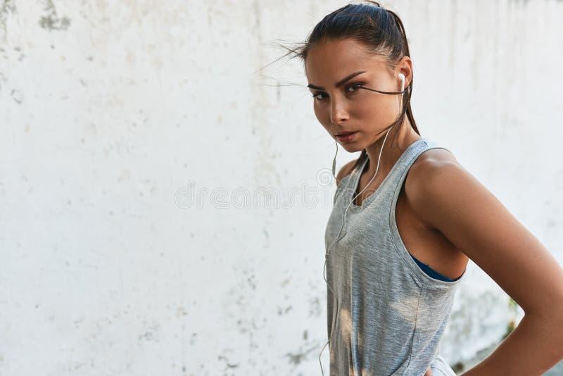Horyzontalny portret młoda poważna dysponowana kobieta pozuje outdoors przeciw betonowej ścianie podczas treningu Sportowy żeński zdjęcia stock