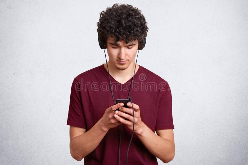 Horyzontalny portret młodego człowieka blogging na telefonie komórkowym i przesyłanie wiadomości podczas gdy słuchający muzykę w  zdjęcia stock