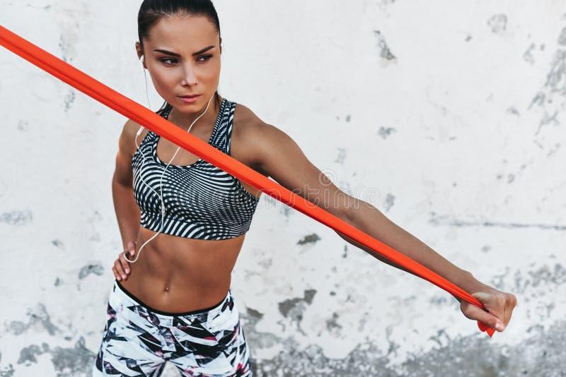Horyzontalny portret sprawności fizycznej kobiety pozycja przeciw betonowej ścianie robi rozciąganiu ćwiczy trzymać czerwonego op fotografia stock