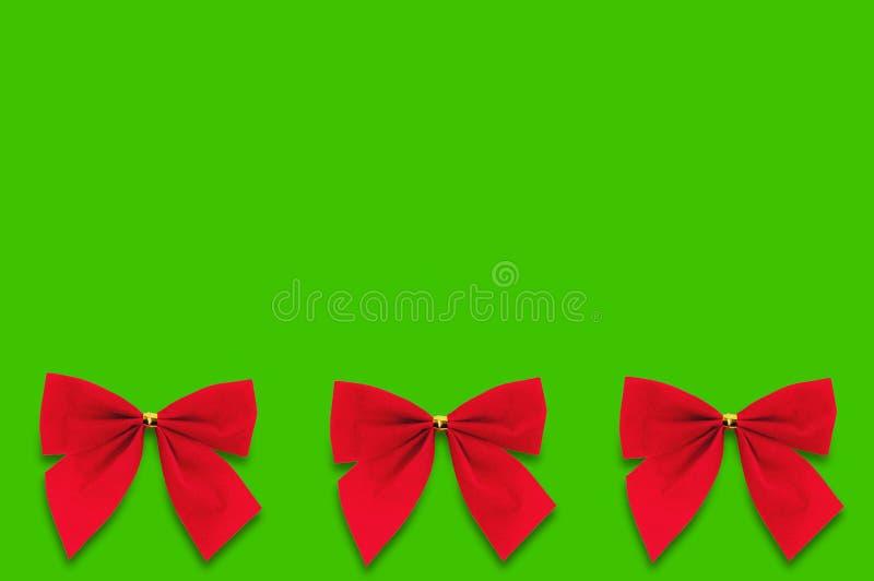 Horyzontalny rząd trzy czerwieni tkaniny łęku na zielonym tle royalty ilustracja