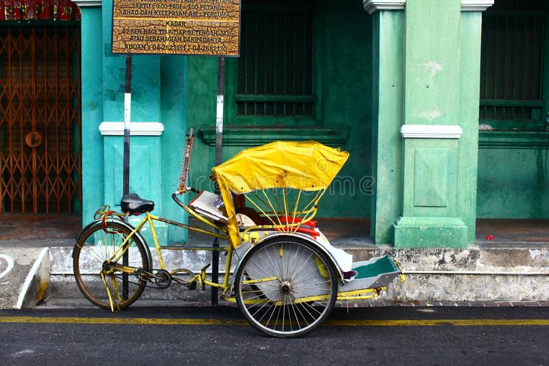 Horyzontalny rzut żółtego cykla rikszy w Georgetown, Malezja zdjęcia stock