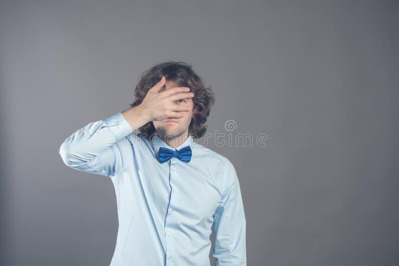 Horyzontalny strzał nieogolone caucasian młode kędzierzawe samiec pokrywy ono przygląda się z palmą, próby chować przez palców, s obraz stock