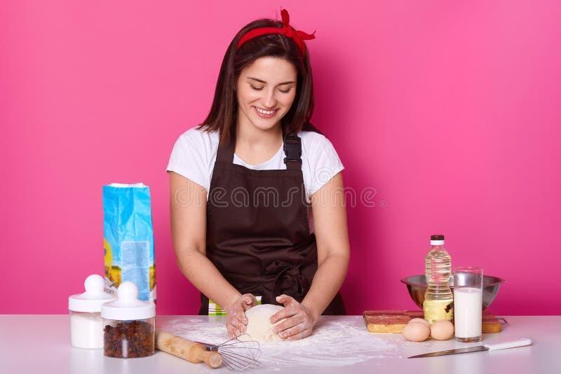 Horyzontalny strzał rozochocona gospodyni domowa ugniata ciasto dla robić pizzy, używa różną składnik mąkę, egss, olej, mleko, by fotografia stock