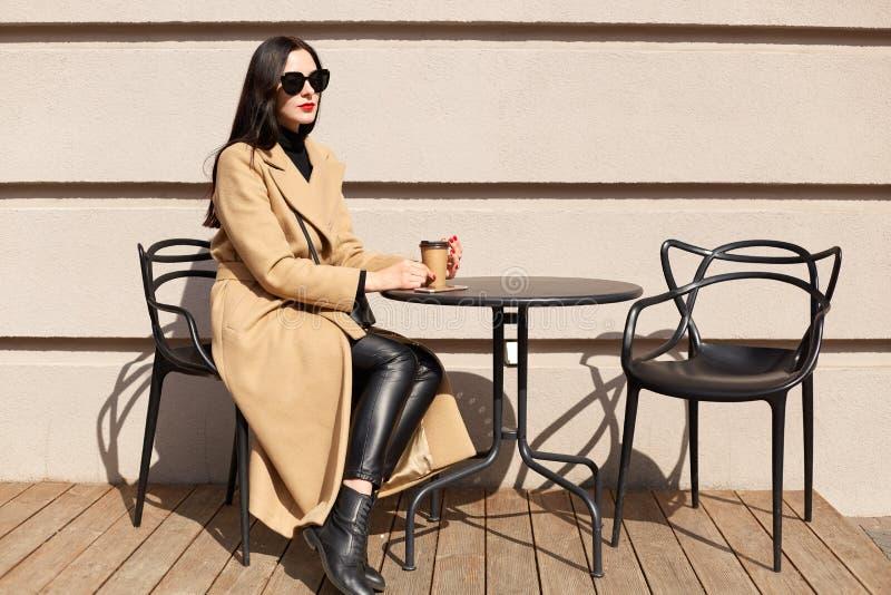 Horyzontalny strzał młoda kobieta z filiżanka napojami kakaowymi przy miasto kawiarni ulicznym tarasem, siedzi przy stołowym i ma obraz royalty free