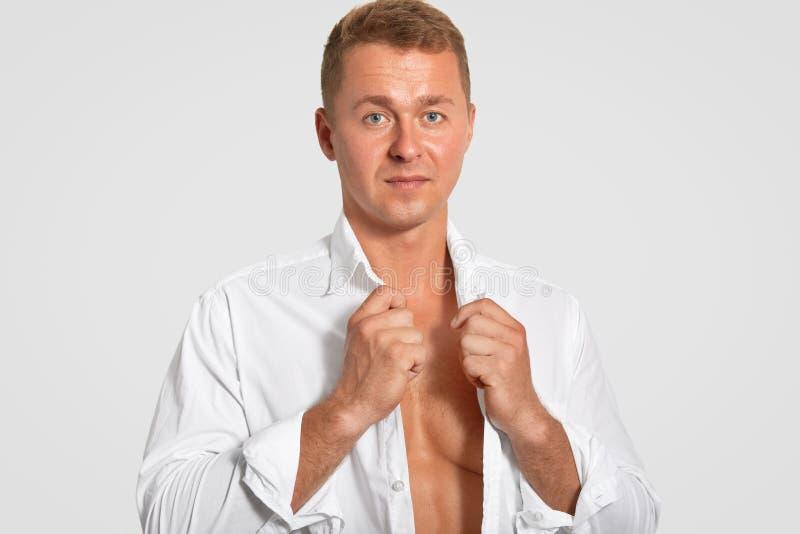 Horyzontalny strzał poważny atrakcyjny mężczyzna jest ubranym białą koszula, pokazuje jego perfect ciało, utrzymania dostosowywał fotografia stock