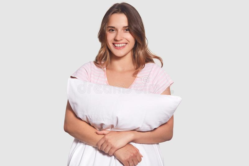 Horyzontalny strzał przyjemna przyglądająca młoda kobieta rozochoconego wyrażenie, obejmuje poduszkę, wyraża pozytywnego uczucie, fotografia stock