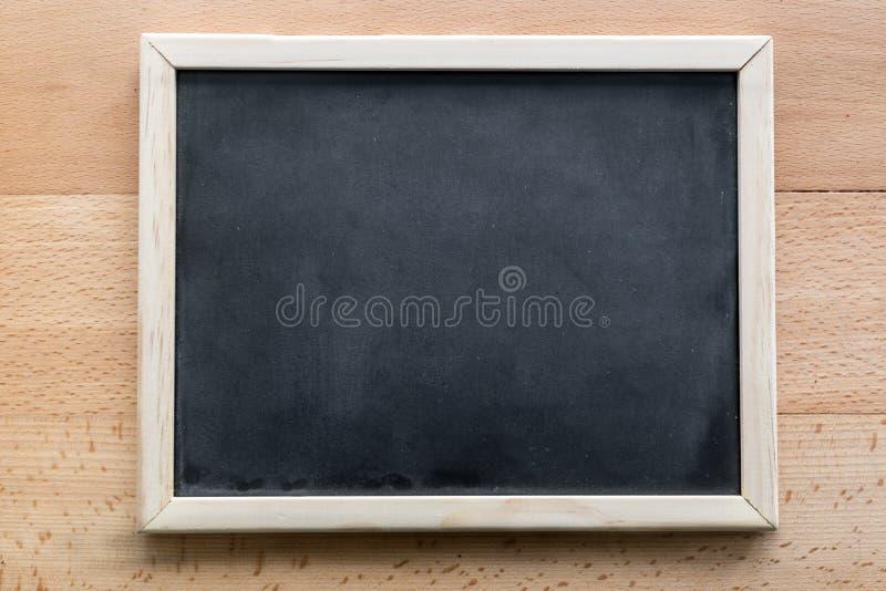 Horyzontalny strzał pusty blackboard lying on the beach na drewnianym tle zdjęcie stock