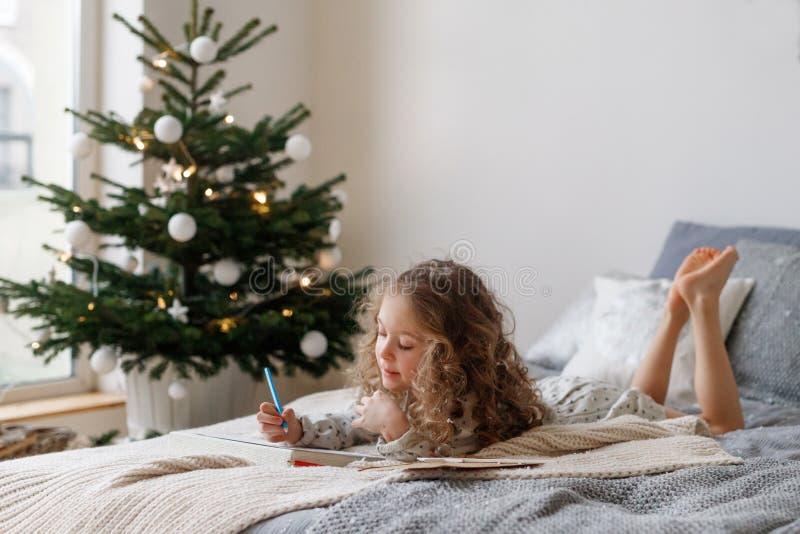 Horyzontalny strzał restful mały żeński dziecko z długimi kędzierzawego włosy spojrzeniami attentively przy prześcieradłem papier zdjęcia royalty free