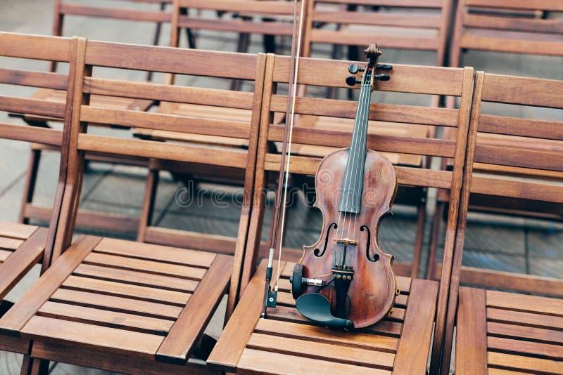 Horyzontalny strzał skrzypce na drewnianym krześle z łękiem Instrumentu muzycznego pojęcie Koncert w na wolnym powietrzu Świątecz zdjęcia royalty free