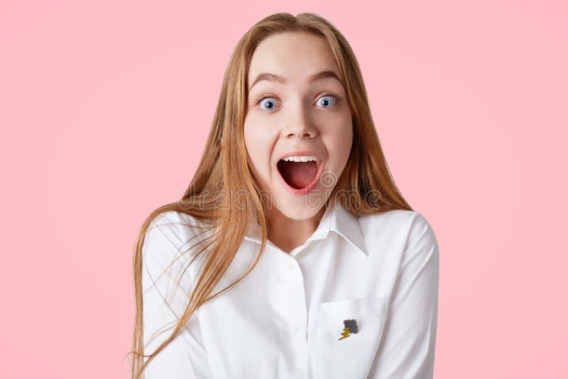Horyzontalny strzał zadziwiająca błękit przyglądająca się kobieta z szokującym z podnieceniem wyrażeniem, utrzymania usta szeroki obrazy stock
