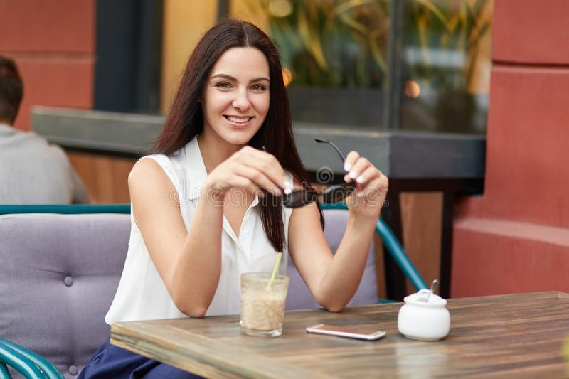 Horyzontalny strzał zrelaksowana piękna Europejska kobieta trzyma cienie, jest ubranym białą bluzkę, długie włosy, pije koktajl,  fotografia stock