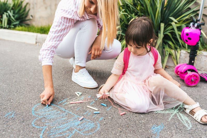 Horyzontalny wizerunek szczęśliwy małej dziewczynki i matki rysunek z pisze kredą na chodniczku Kaukaska żeńska sztuka wraz z dzi obraz stock