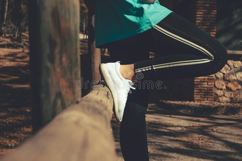 Horyzontalny zdobycz kobieta odpoczywa w drewnianym płotowym jest ubranym sporcie odziewa fotografia stock