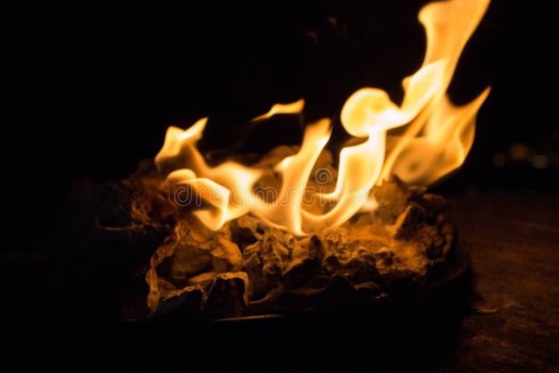 E 橙色火焰关闭 r r 篝火在黑暗中 免版税库存照片