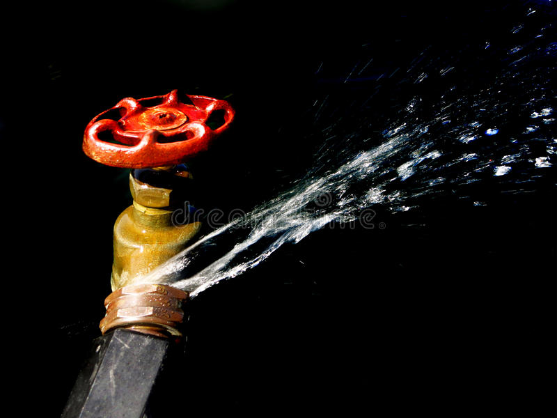 Hose Faucet Connection Leaking and Squirting Water. Detail of hose faucet connection leaking and squirting water spray royalty free stock image