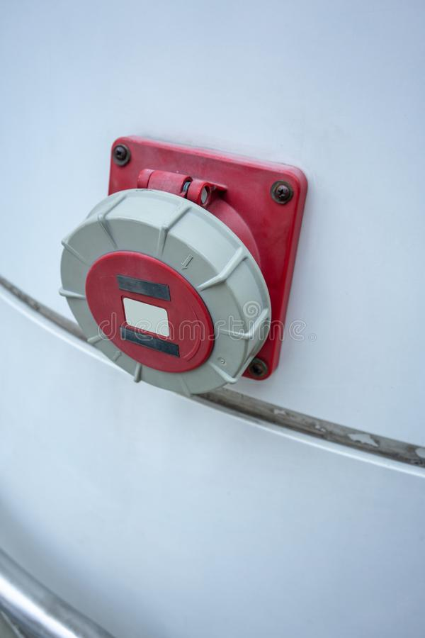 Hose valve for fire protection equipment mounted from building. White wall with red splitter hose connector stock photo