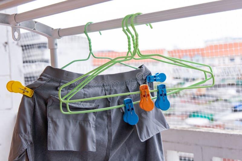 Hosen, die an der Wäscherei Innen hängen lizenzfreie stockbilder