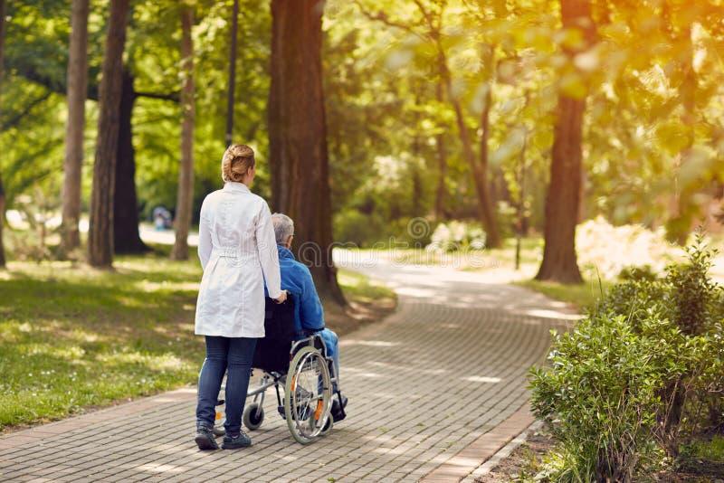 Nurse helping elderly man on wheelchair outdoor royalty free stock photography